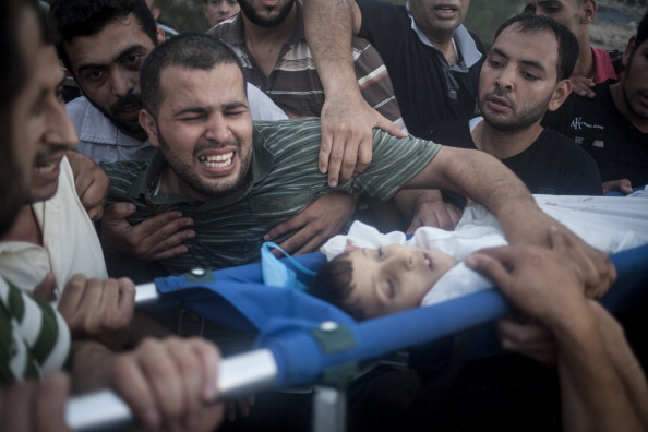 A father of one of the three child victims of Israeli airstrikes in Gaza cries during the funeral. The series of Israeli airstrikes in the Gaza strip kills more and more innocent victims, July 17, 2014. (Photo: Cesar Gorriz / Getty Images)